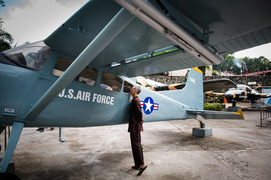 Man peers into a plane artifact at the War Remnants Museum in HCMC.